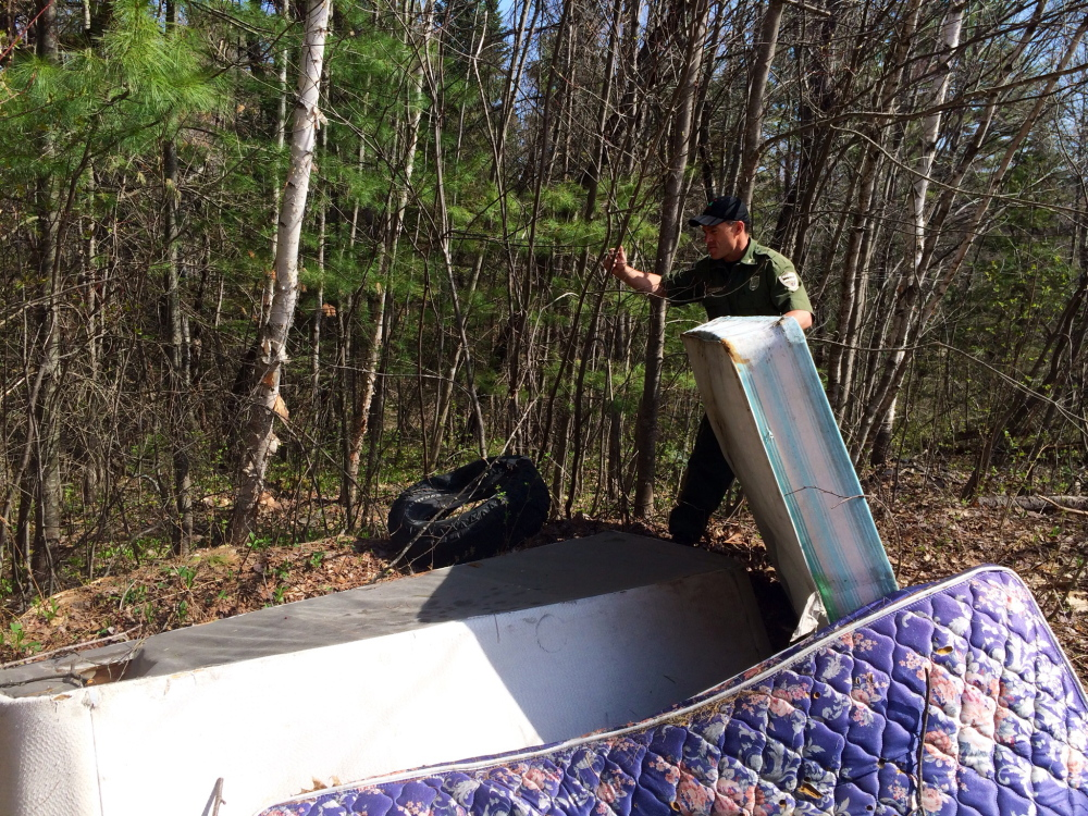 Game Warden Tom McKenny sorts through a pile of mattresses illegally dumped on private property off Martin Stream Road in Fairfield. Reports of illegal dumping have grown from just 2 to 3 percent of all complaints to forest rangers about 20 years ago to 13 percent of all calls in 2013.