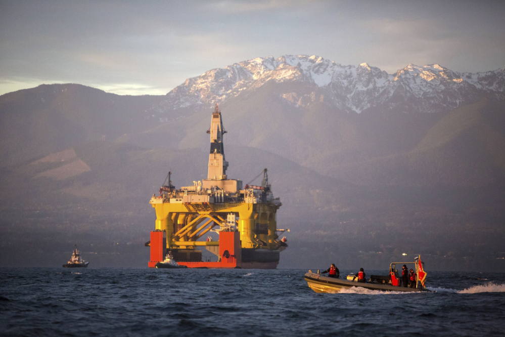 Against the backdrop of the Olympic Mountains, a small boat crosses in front of an oil drilling rig as it arrives in Port Angeles, Wash., aboard a transport ship after traveling across the Pacific.