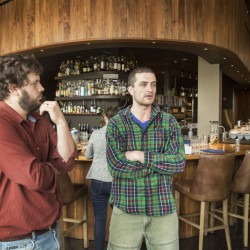 Andrew Taylor, left, and Mike Wiley, co-owners of Hugo's, Eventide Oyster Co. and The Honey Paw with Arlin Smith, talk about their disagreement with food blogger John Golden in the dining area of Hugo's on Monday.