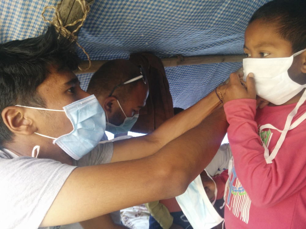 Surya Karki, left, a native of Nepal and a student at College of the Atlantic in Bar Harbor, assists a Nepalese child in securing a face mask in the village of Taudaha.