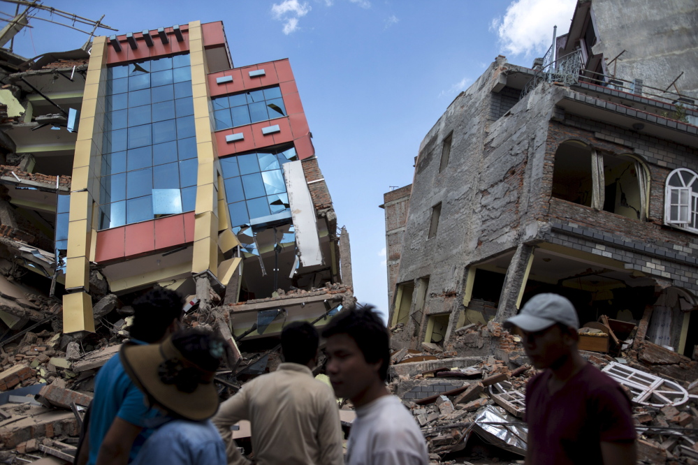 People walk near a pair of damaged buildings after a 7.3-magnitude earthquake struck in Kathmandu, Nepal, on Tuesday. Dozens more were reported killed in the latest jolt, which spread panic among residents following the devastating quake less than three weeks ago.