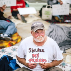 Mark Parent, who is homeless, holds a sign outside Portland City Hall on Tuesday. Whitney Hayward/Staff Photographer