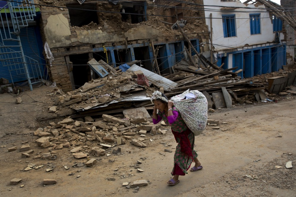 A Nepalese woman carrying belongings walks past a damaged house in Chautara, Nepal, Wednesday.