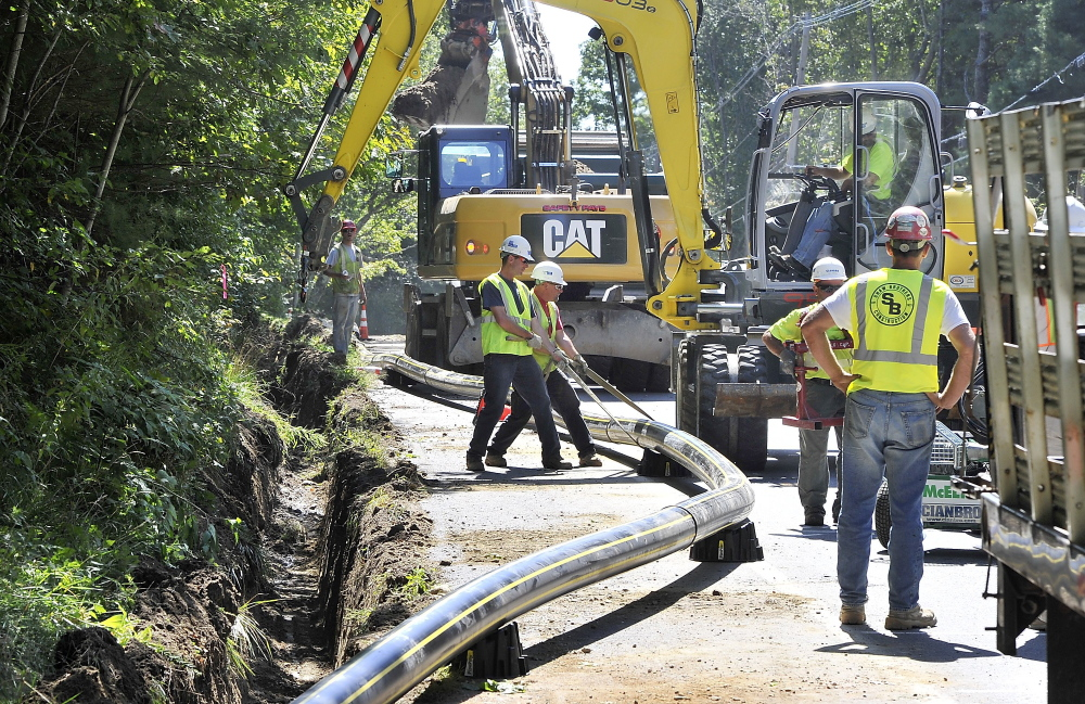 Subcontractor crews get a pipe into position for burial in a trench along Route 88 in Cumberland last year. Summit Natural Gas of Maine says it didn't anticipate how little Mainers knew about natural gas when it arrived here in 2012.