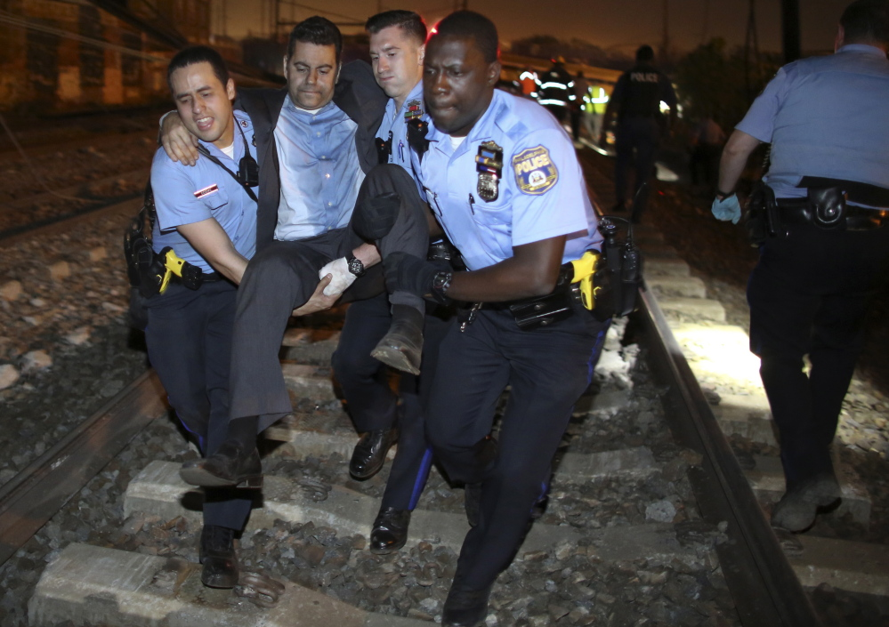 Emergency personnel help a passenger at the scene of a train wreck just north of Philadelphia, Tuesday. Seven people were killed and more than 200 were injured.