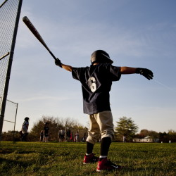"""Kory Rolbiecki, 7, of Windham swings in the on-deck circle before his first at-bat in a Little League game on Thursday. It was his first game since his former coach Chris """"Pepe"""" Doucette passed away. Gabe Souza/Staff Photographer"""