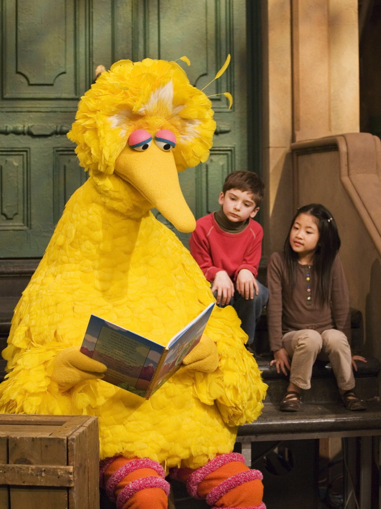 "Big Bird, voiced by Caroll Spinney, reads to children during a 2008 taping of ""Sesame Street."""