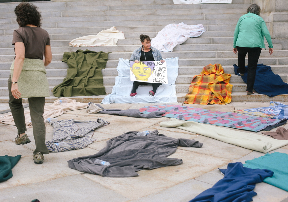Joanie Klayman, left, and Caroline Fernandes, right, both of Preble Street, place blankets on the steps of Portland City Hall, while Mary Jo Skofield of Homeless Voices for Justice holds a sign Tuesday in protest of potential budgetary cuts to homeless overflow housing in Portland. Press Herald file photo