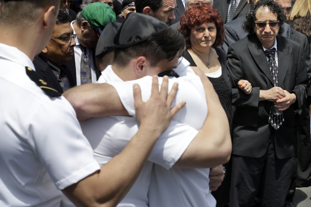 Howard and Susan Zemser, right, watch Friday as midshipmen embrace during the funeral service for their son, U.S. Naval Academy midshipman Justin Zemser, at Boulevard-Riverside-Hewlett Chapel in Hewlett, N.Y. The sophomore, 20, was traveling to his home in New York City when he was killed in Tuesday's derailment in Philadelphia.