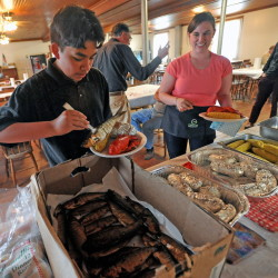 Fernando Cuares, 15, and Darcy Dow help themselves to smoked alewives and lobster.