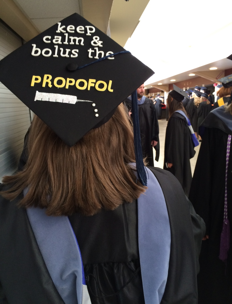 Brittney Painter makes a reference to her master of science in nurse anesthesia on her mortarboard as she waits to graduate at Cross Insurance Arena in Portland on Saturday. Painter was one of 1,449 graduates who received degrees at the University of New England's 180th commencement ceremony.