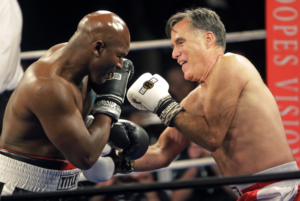 Romney, right, throws punches at Holyfield before ending the fight after just two rounds.