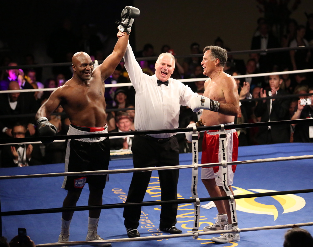 Five-time heavyweight boxing champion Evander Holyfield, left, is declared the winner against Former Republican presidential candidate Mitt Romney during a charity fight night event Friday.