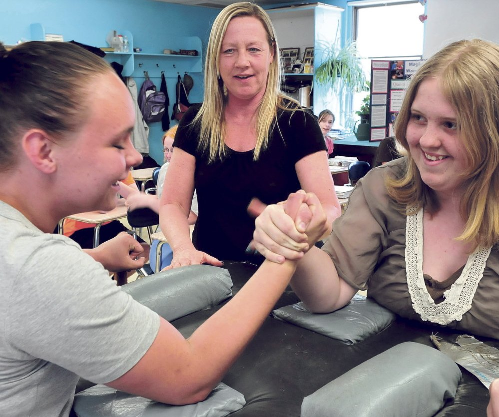 Athens Community School teacher Tammy Moulton was one of several approached about taking over as principal, but she didn't want to stop teaching. Here she watches Mia Braley, left, and Sylvia Andersen arm wrestle during a community volunteer visit by the wrestling instructor.