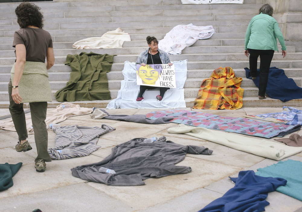 Joanie Klayman, left, and Caroline Fernandes, right, both of Preble Street, place blankets on the steps of Portland City Hall last Tuesday, while Mary Jo Skofield from Homeless Voices for Justice holds a sign in protest of potential budget cuts to homeless overflow shelters in Portland.