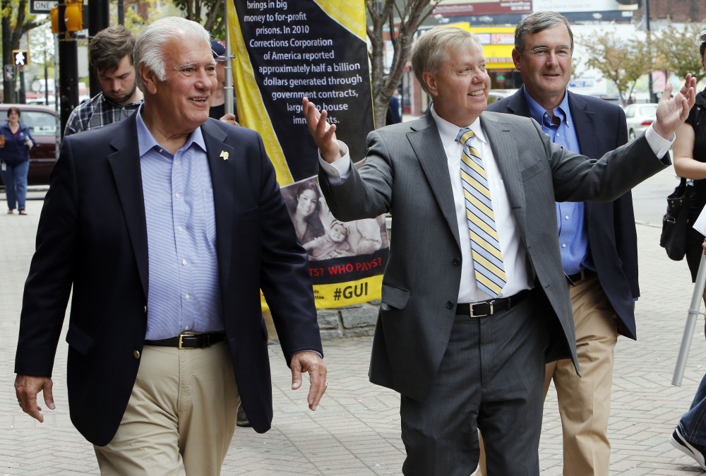 Sen. Lindsey Graham, R-S.C., accompanied by Manchester, N.H., Mayor Ted Gatsas, takes a walking tour of downtown Manchester, N.H., Friday, May 15, 2015. Graham is considering a run for the Republican nomination for president.