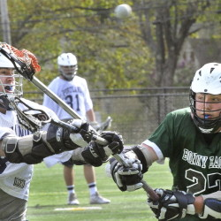 Zack Klein of Bonny Eagle, right, tries to block a shot on goal by Robert Nolan of Portland during Portland's 15-6 victory Wednesday in a schoolboy lacrosse game at Deering High.