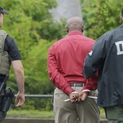 An unidentified man, center, is escorted from a medical clinic in Little Rock, Ark., by Drug Enforcement Administration officers on Wednesday.