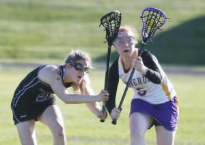 Emily Duff of Cheverus, right, keeps her eyes on the ball Thursday while pressured by Claudia Folger of Marshwood during their schoolgirl lacrosse game in Portland. Marshwood came away with a 14-2 victory.
