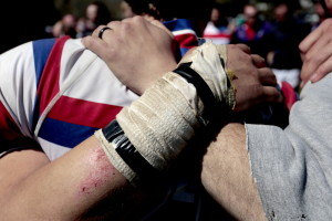 After the Portland Rugby Football Club lost to the Mystic River Rugby Club in a recent match, the team banded together to talk as a group behind Deering High School, many of them still wearing scars from the game.