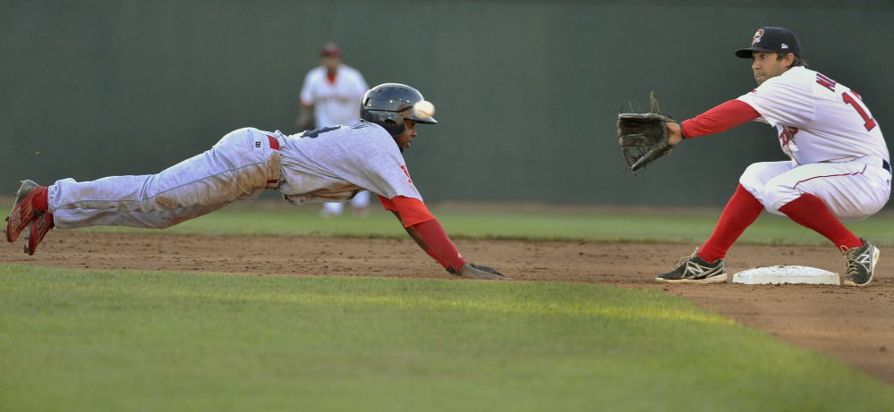 Reading's Roman Quinn dives back into second base as Portland's Mike Miller waits for the throw Friday at Hadlock Field.