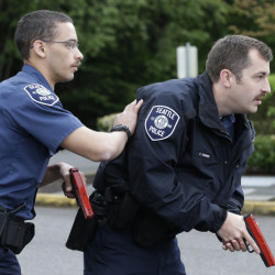 Seattle police recruits Tre Smith, left, and Travis Duennes work together in a practice scenario at the Washington State Criminal Justice Training Commission in Burien.