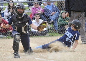 York's Kiley Blondin slides safely into home as Yarmouth catcher Kallie Hutchinson gets a late throw. York went on to win and raise its record to 13-0. John Patriquin/Staff Photographer