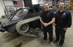 "Mike Howe, left, and Geoff Howe show off their Ripsaw EV 2 in Waterboro. One of their vehicles earned an extended action sequence in ""Mad Max: Fury Road."""