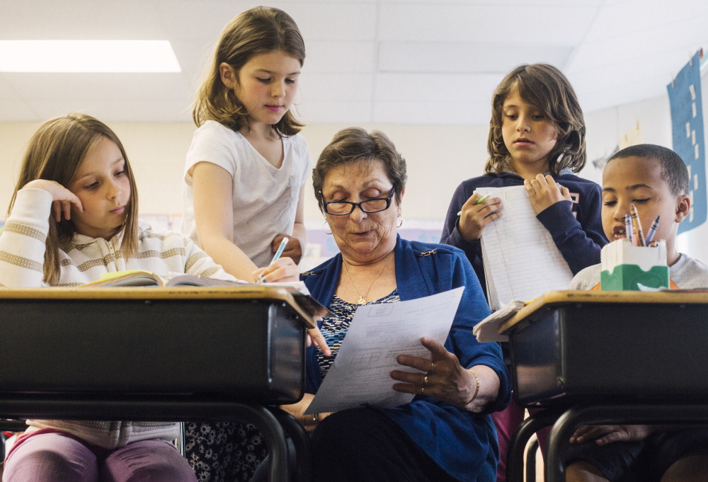 """Foster Grandparent Fran Seeley helps third-graders, from left, Alexus Chapman, Charlotte Libby, Lucy Tidd and Donald Enman with math at Lyseth Elementary School in Portland on Tuesday. """"Sometimes with math I get a little bit like I don't believe in myself, but now I feel like I'm getting better,"""" Charlotte said."""