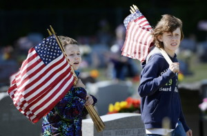 Carly Belanger 9, and Travis Belanger 13, both of Saco, look for veterans' graves to put flags on at St. Ignatius Cemetery in Sanford on Saturday.  Shawn Patrick Ouellette/Staff Photographer
