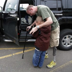 In this 2008 photo, retired Minnesota National Guard Sgt. John Kriesel comforts his son. Kriesel lost both his legs when a roadside bomb went off near Fallujah, Iraq, in 2006.