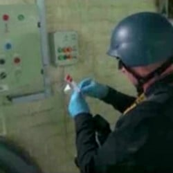 This file image made from video broadcast on Syrian State Television purports to show an expert taking samples at a chemical weapons plant at an unknown location in Syria.
