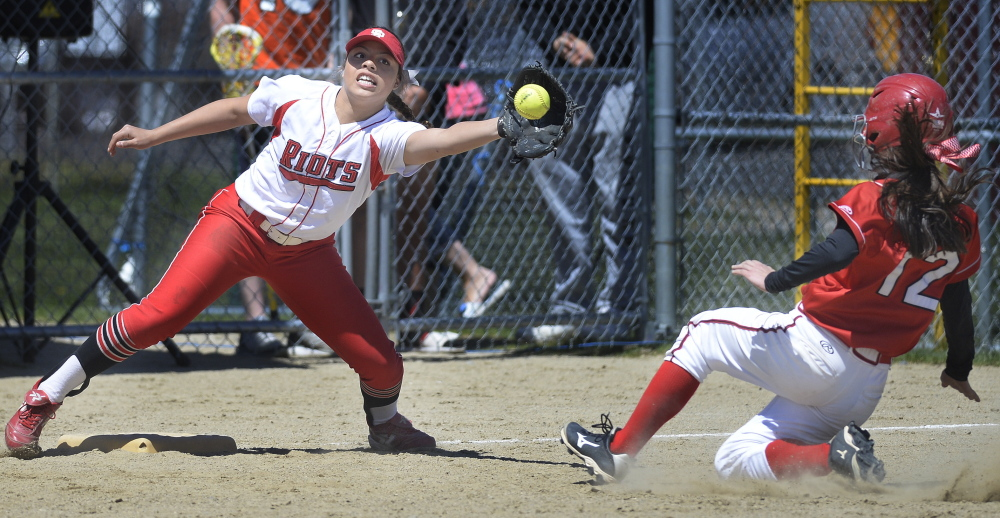 Laurine German of South Portland stretches for a throw as Scarborough's Hannah Ricker slides safely into third base during their SMAA softball game Saturday in Scarborough. The hosts improved to 13-0 with a 5-4 victory.