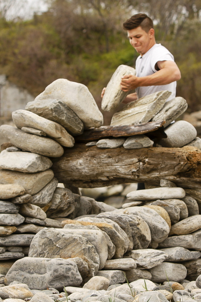 Morales-Walsh practices his art of stone arch building at Fort Williams Park in Cape Elizabeth. He says he enjoys working outside to create something he finds beautiful.
