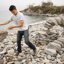 Daniel Morales-Walsh, 25, of South Portland, tosses aside a log he used as a form to create an arch at Fort Williams Park in Cape Elizabeth.