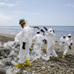 Workers gather oil-contaminated sand bags at Refugio State Beach, north of Goleta, Calif.