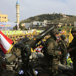 Hezbollah fighters stand guard during a rally Sunday in Nabatiyeh, Lebanon, celebrating the country's Liberation Day. The leader of Hezbollah said his militants will expand their support of government forces in the Syrian civil war.