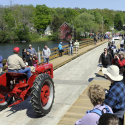 A tractor is driven across the floating bridge during a reopening parade in Brookfield, Vt., on Saturday. The bridge is believed to be the only one of its kind in the country.
