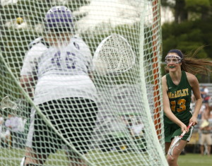 Molly Barr of McAuley watches her shot head toward the goal in the second half Monday as Evelyn Molina guards the net for Deering. McAuley rallied for a 13-12 victory.