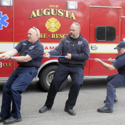 Augusta Fire Department paramedics Randy Gordon, left, Jeremy Manzer and Kurt Gordon get pulled inside Hartford Fire Station in Augusta by colleagues during rescue training.