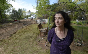 Julie Claffey stands near the memorial gardens where she buried her husband's ashes at her Scarborough home. When she tried to block her neighbors from putting in a driveway on their property at left, the town did a review, then stopped interceding for her.