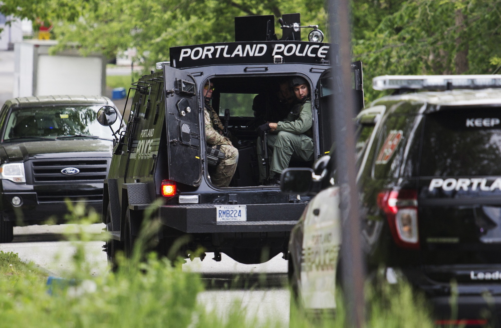 Members of the Portland police Special Reaction Team wait outside a house during Tuesday's raid near Presumpscot Elementary School.