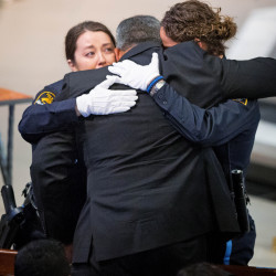 Two Omaha police officers embrace Hector Orozco, the husband of Kerrie Orozco, who was slain when she answered the call to help another officer.