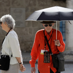 Bill Berkson of New York, uses an umbrella as protection from the sun as he tours Old Havana, Cuba, on Sunday. Berkson, whose trip coincided with the Havana Biennial Art Fair, went to Cuba directly from the U.S. with all necessary permissions under a cultural program visit. The Associated Press