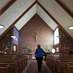 Maryellen Rogers walks down the center aisle of the St. Frances Xavier Cabrini Roman  Catholic Church in Scituate, Mass., on May 20. Parishioners have occupied the church, night and day, for almost 11 years, hoping the Boston archdiocese will restore their parish's standing or sell them the building outright.