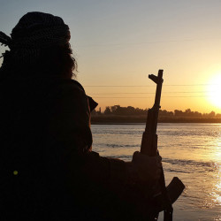 In a photo released by a militant website, an Islamic State jihadi holds an AK-47 as he relaxes by the banks of the Euphrates River in Raqqa, Syria.
