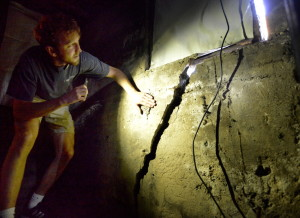 Brent Adler, who with his business partner Liv Chase owns the apartment building at 48 Hancock St., illuminates cracks that formed in the structure's foundation resulting from work being done at Seaport Lofts in Portland's East End. The city wants the developer to provide an engineering study before work on the project can resume.