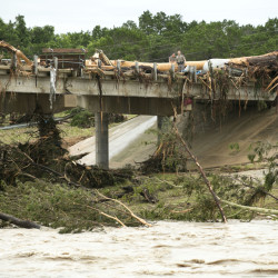 A large tree rests on the Hwy 12 bridge over the Blanco River in Wimberley, Texas, Sunday May 24, 2015. Flooding in Texas and Oklahoma has led to numerous evacuations.