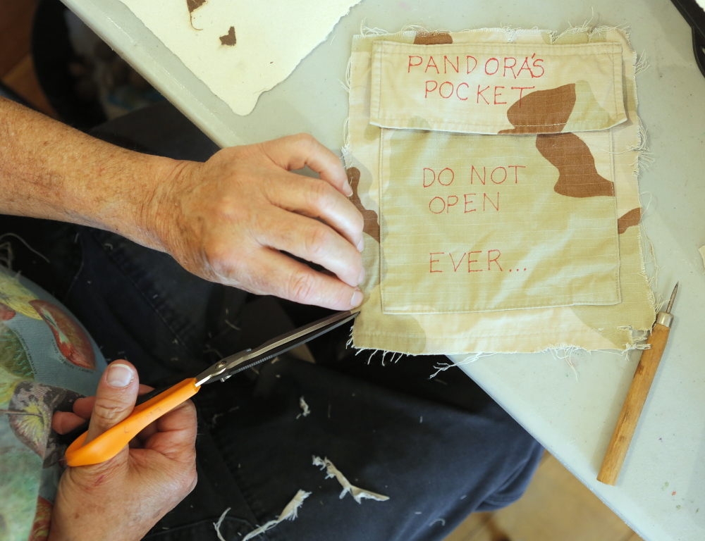 Veteran Terry Grasse cuts an edge of a military uniform pocket while creating his art. The art of the veterans gathered in Deer Isle will hang on the walls of a Haystack center building Friday night through Sunday.