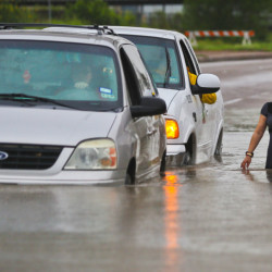 A municipal vehicle pushes a stranded van that attempted to make it through the high waters along Mexico Boulevard in Brownsville, Texas, on Thursday.